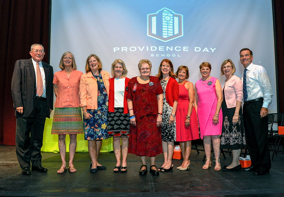Dr. Glyn Cowlishaw (right), Head of School, stands with the 9 of the 10 retiring faculty and staff honored during a reception in the McMahon Fine Arts Center theater May 12 at Providence Day School. Pictured (from left) are Middle School Head Sam Caudill, Summer Programs Director Nancy Stockton, Admissions Associate Director Barbara Bodycott, Lower School Computer Science Department Chair Beth Hunter, Lower School Librarian Debra Wilhoit, Extended Day teacher Judy Bennett, Lower School Head Kay Montross, 3rd-grade teacher Marsha Small and Middle School math teacher Beth Ralston. Not pictured is Janis Roten of the Business Office. (Photo credit: Mike McCarn / Providence Day School)